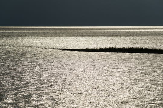 Light from the sun reflects off of Lake Okeechobee, providing stark contrast with storm clouds seen over the lake from Port Mayaca Lock and Dam on Monday, June 11, 2019, in Martin County.