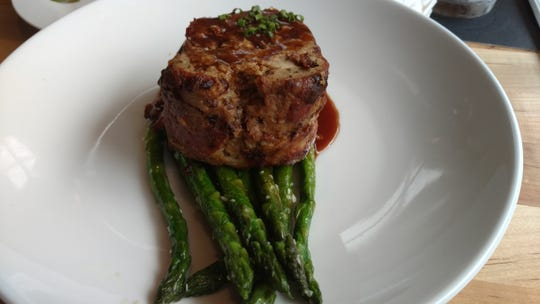 Michael's on 7th presents a generous portion of deliciously flavored meatloaf lovingly placed upon a rich brown pool of demi-glace and served atop asparagus.