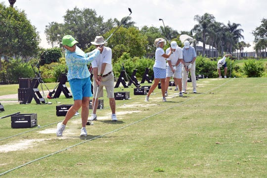 Golfers warm up on the practice tee at Grand Harbor's 15th annual Community Outreach Golf Classic.