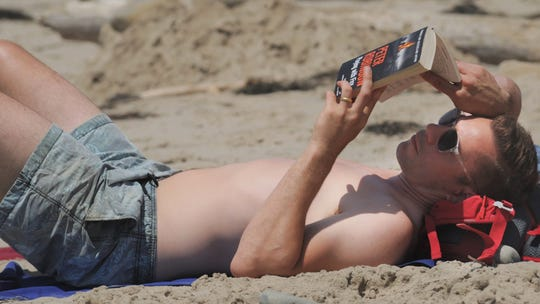 Richard Furze, visiting from England, enjoys reading a book on the beach near the Ventura Pier during a past heat wave.