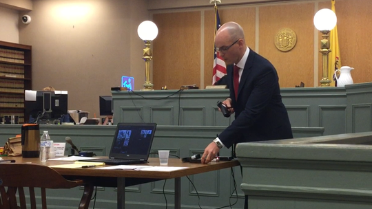 Cumberland County Assistant Prosecutor Charles J. Wettstein handles the .40-caliber Beretta pistol used to kill Ivan Scott Strayer II in Vineland in 2016. The pistol was among exhibits for jurors during closing arguments in the Superior court trial on Tuesday.