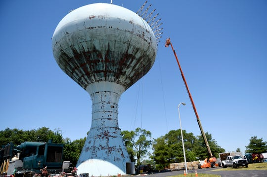 Workers prep the surface of the water tower, located at the corner of North Main Road and East Oak Road in Vineland on Tuesday, June 11, 2019.