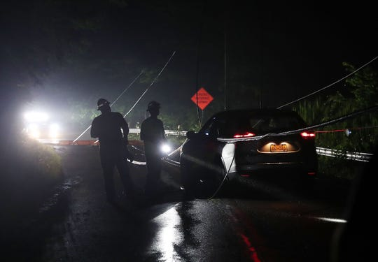 NYSEG workers remove de-energized power lines from a vehicle on Fields Lane in the town of Southeast on June 11, 2019. Rain and wind overnight caused a tree to fall and take a utility pole and wires down with it. The driver was told to stay in her car until the power could be cut. After a 45-minute wait the uninjured driver was able to back out and continue her ride home.