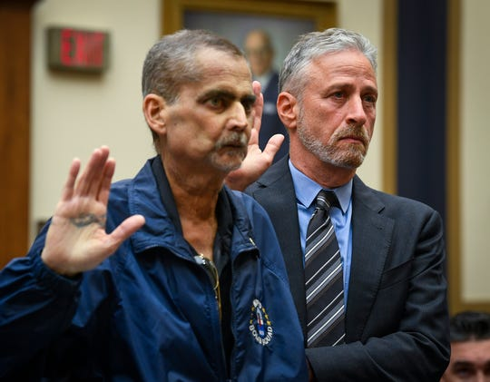 Jon Stewart helps Luis Alvarez, a retired Detective and 9/11 Responder with the New York Police Department, as they are sworn before testimony in front of the House Judiciary Committee on the need to reauthorize the September 11th Victim Compensation Fund on June 11, 2019 in Washington, DC.