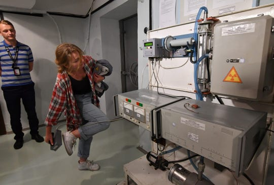 A visitor check her shoes with geiger counter during a tour of the underground shelter of Chernobyl nuclear power plant on June 7, 2019. A geiger counter is a device used to measure radiation. The underground shelter held the first meetings of the official commission that handled the subsequences of the disaster in April 1986.