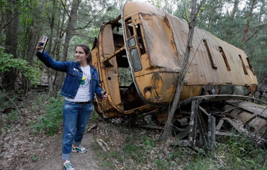 A visitor takes a selfie with an abandoned bus during a tour in Chernobyl, Ukraine.