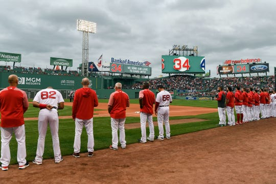 The Red Sox stand for a moment of silence honoring former team member David Ortiz before a game against the Rangers at Fenway Park. Ortiz was shot and injured in his native Dominican Republic.