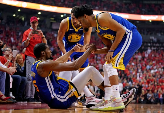 Kevin Durant is helped up by Quinn Cook and Klay Thompson.