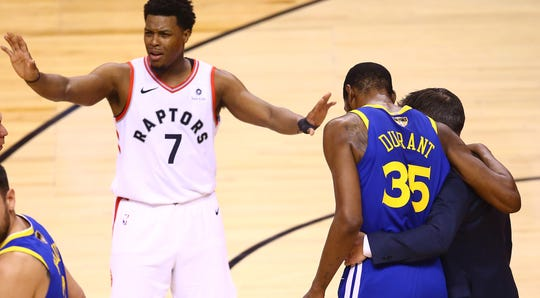 Kyle Lowry quiets the crowd as Kevin Durant is helped off the court.