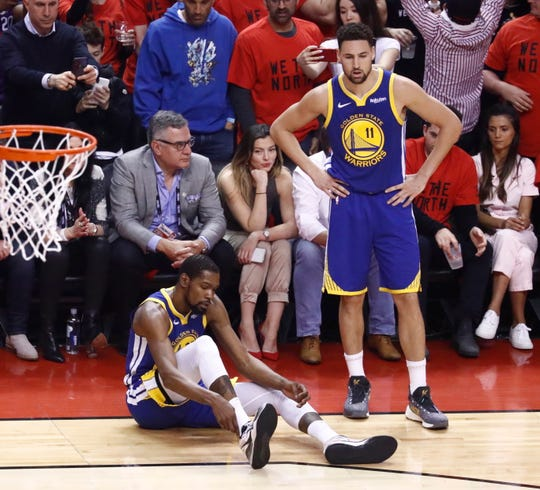 Kevin Durant holds on to his leg as Klay Thompson looks on.