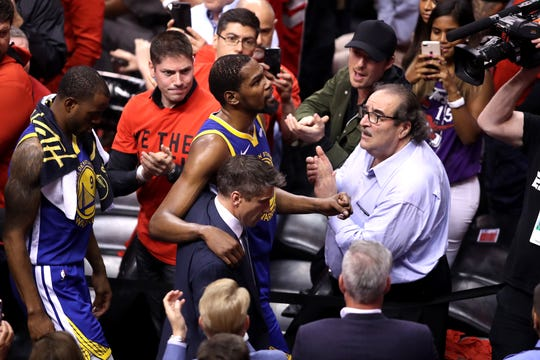 Kevin Durant is helped off the court as Raptors fans give him a round of applause.