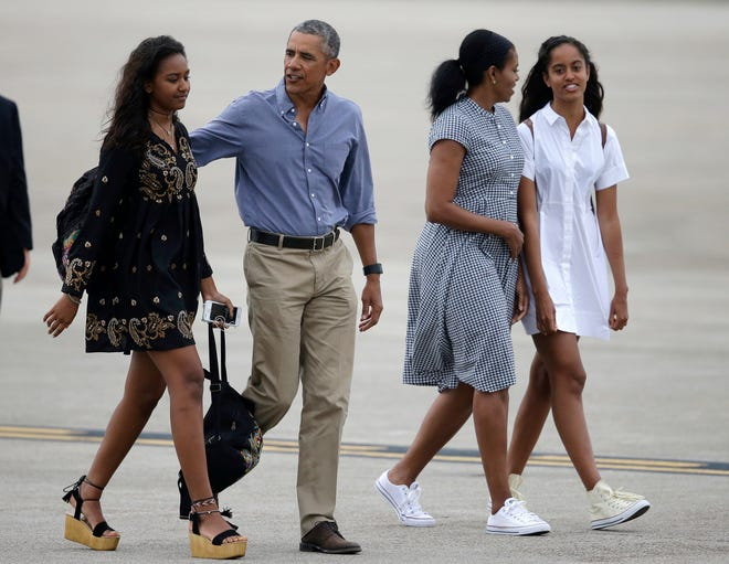 President Barack Obama, center, and first lady Michelle Obama, second from right, walk with their daughters, Sasha, left, and Malia on the tarmac to board Air Force One at the Cape Cod Coast Guard Station, in Bourne, Mass., on Aug. 21, 2016.