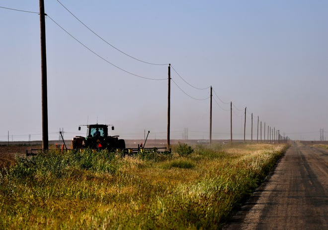A tractor planting cotton seed drives along the edge of a field on FM 1661 between Anson and Hamlin on Wednesday. Wet spring weather has delayed planting for many area farmers who are now facing a late-June crop insurance deadline for getting cotton seed in the ground.