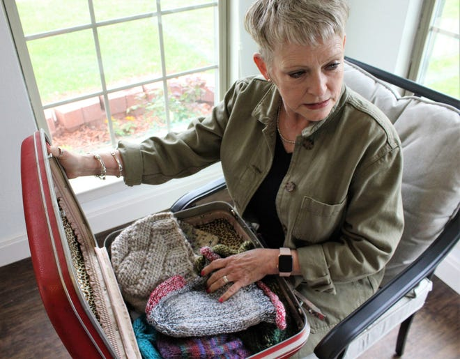 Candy Key with her suitcase full of knitted caps at Houses for Healing in north Abilene.
