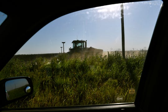 A tractor planting cotton seed drives along the edge of a field on FM 1661 between Anson and Hamlin on Wednesday. Wet spring weather has delayed planting for many area farmers.