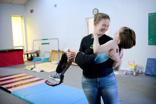 Coach Jennifer Nikitopoulos picks up Zoe Smith, 10, to prove to her that she isn't heavy as they joke around after practice at Halo Gymnastics on June 7, 2019. Zoe says that her coaches are more positive and encouraging than coaches she has had in the past.