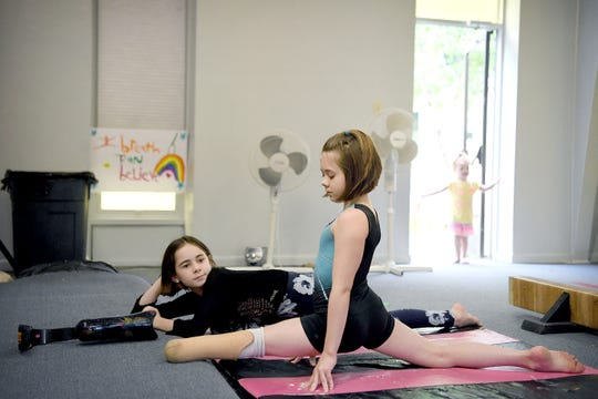 Zoe Smith, 10, stretches with her sister, Fatima, 11, at Halo Gymnastics, located in a church in Candler, on June 7, 2019. Zoe often calls on Fatima to explain to other kids about her leg and answer the questions she often gets.