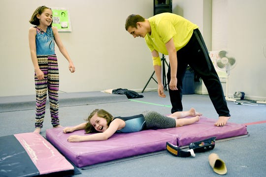 "Fatima Smith, 11, left, and Jake Sellers, 15, laugh as they help Zoe Smith, 10, who is very flexible, stretch at the end of practice at Halo Gymnastics on June 10, 2019. ""I love how your team is always there for you, and you're always there for them,"" Zoe said about gymnastics."