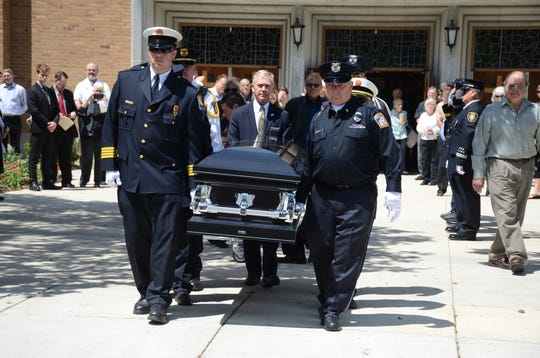 Pallbearers carry the body of Murray Switzer from the church following his funeral on Wednesday.