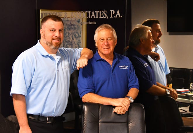 Ryan Jotkoff and his dad, Alan Jotkoff, are pictured in the conference room of the West Melbourne location of Jotkoff Financial Services, Inc.