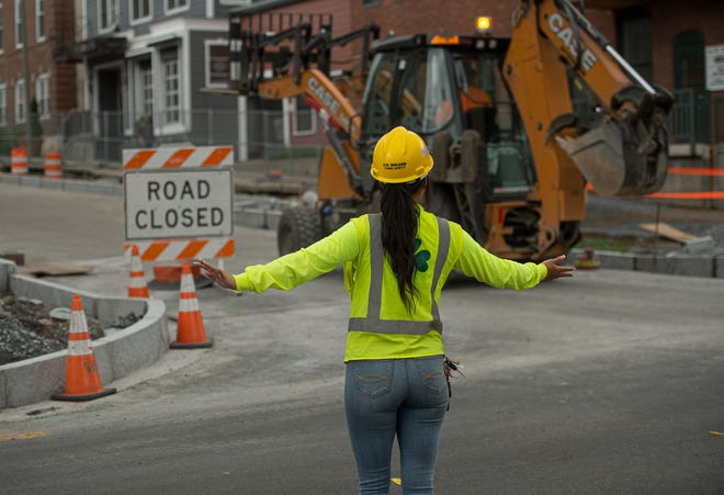 A construction worker directs traffic on King Street as a backhoe operates on St. Paul Street June 11, 2019.