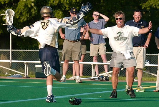 Essex's Jason Weischedel (left) runs into the arms of coach Dean Corkum after the Hornets defeated CVU in the boys' Division I lacrosse state championships in Burlington on Friday June 8, 2007.