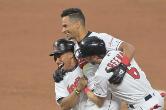 Jun 11, 2019; Cleveland, OH, USA; Cleveland Indians left fielder Oscar Mercado (35), center, celebrates his game-winning single with shortstop Francisco Lindor (12) and second baseman Mike Freeman (6) in the tenth inning against the Cincinnati Reds at Progressive Field. Mandatory Credit: David Richard-USA TODAY Sports