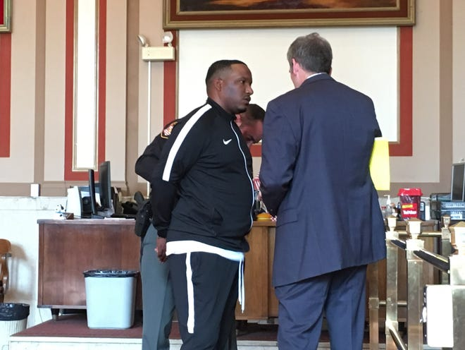 Stanley Jackson, at center, talks to his attorney, Bill Gallagher, after being sentenced to two years in prison for marijuana trafficking on June 12, 2019. A Hamilton County sheriff's deputy is putting handcuffs on Jackson.