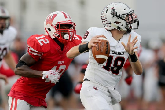 Lakota West Firebirds linebacker Daved Jones Jr. (12) pressures Oak Hills Highlanders quarterback Ethan Myers (18) in the first quarter during a high school football game between the Oak Hills Highlanders and Lakota West Firebirds, Friday, Sept. 21, 2018, at Lakota West High School in West Chester Township, Ohio.