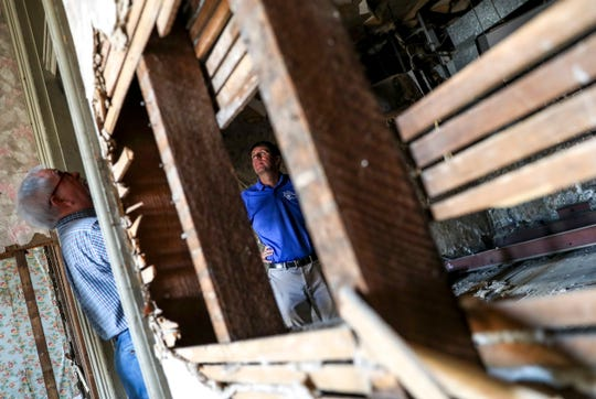 Gary Norris, left, and Brent Clemmons, design review coordinator, right, look up at a damaged portion of the ceiling during a walk through visit at the Dabbs Building in Clarksville, Tenn., on Wednesday, June 12, 2019.