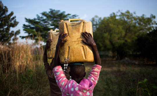 A child walking home after filling up her jerry can, which weighs 45 lbs, with dirty water.