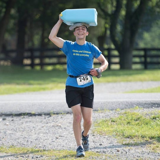 James Leitner carrying 45 lbs of water on his head for one of his monthly marathons.