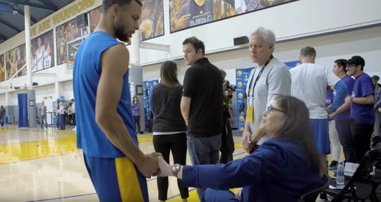 Golden State Warriors star Steph Curry shakes hands with Denise Long, the Iowa native who was the first woman ever drafted into the NBA by the then-San Francisco Warriors.