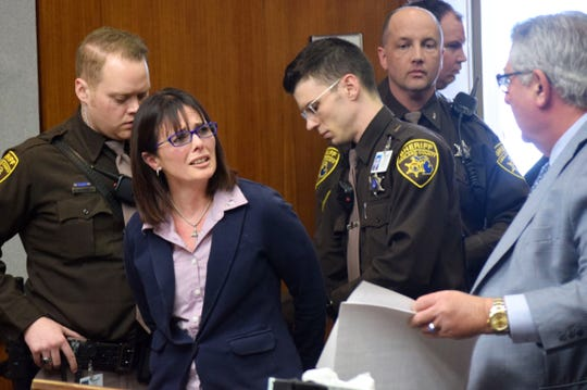 Tina Talbot looks to her attorney, Jerome Sabbota, as Oakland County Sheriff's deputies put her in handcuffs to escort her out of an Oakland County courtroom after she is sentenced on April 4, 2019. Talbot was sentenced to 20-months-15 years for the shooting death of her husband, Milosz Szczepanowicz.