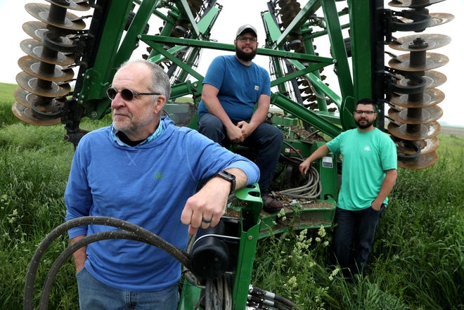 From left, Mike Fike, owner of Fike Farms, Chris McCallister and Chris Coscarelli pose for a photo in the overgrown grass by a vertical disc tiller at Fike Farms in Jasper, Michigan on Wednesday, May 29, 2019.