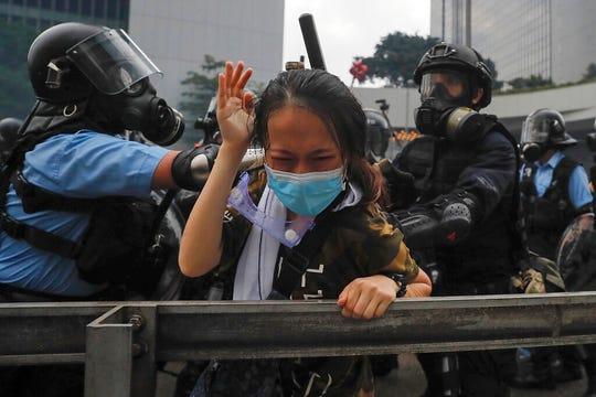 A protester reacts as she tackled by riot police during a massive demonstration outside the Legislative Council in Hong Kong, Wednesday, June 12, 2019.