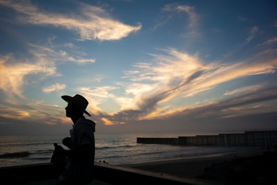 A man looks out near where the border wall, right, separating San Diego from Tijuana, Mexico, meets the Pacific Ocean, June 11 in Tijuana.