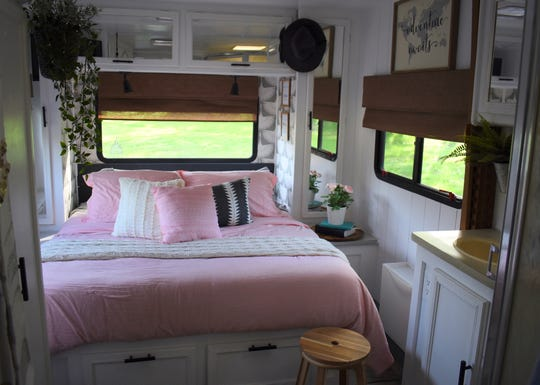 "Pops of pink, green plants, hidden storage and cozy touches mark the main sleeping area.   DIY blogger Sarah Lemp shows off the 1994 Horizon 29-foot ""class C"" RV that she renovated, her 5th such project, at her home in Livonia, Michigan on June 12, 2019.  Lemp specializes in flipping RVs like this one, which her 7-person family took on a trip to Disney World  recently."