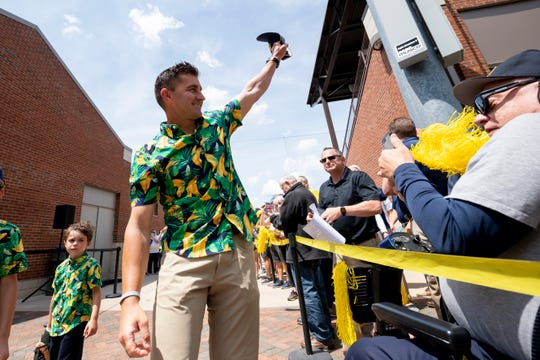 Head coach Erik Bakich waves goodbye as the Michigan baseball team is sent off by fans from Ray Fisher Stadium to the College World Series in Omaha.