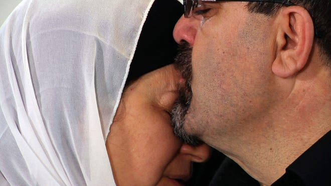 Namee Barakat hugs a relative during a news conference in Raleigh, N.C., about the death of his son, Deah, his daughter-in-law and her sister.