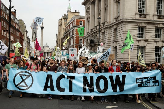 Climate change protesters march in April in London. Britain's prime minister has announced plans to eliminate the country's net contribution to climate change by 2050. Theresa May said the plan will be put before Parliament Wednesday, June 12.