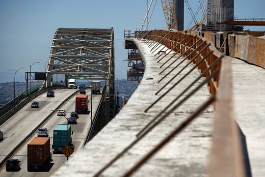 In this July 2, 2018, file photo, traffic moves on the old Gerald Desmond Bridge next to its replacement bridge under construction in Long Beach, Calif. President Donald Trump's tariffs are taxes paid by American importers and are typically passed along to their customers. They can provoke retaliatory tariffs on U.S. exports.