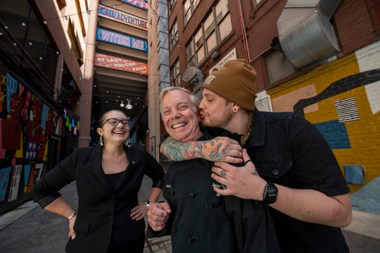 Jimmy Schmidt, center, owner of Lucky Noble BBQ, goofs around with his daughter Taylor Rene, left, a sommelier at Roast, and his son Stephen, the executive chef at Standby, in the Belt alleyway in Detroit.