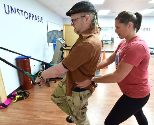 M. Thomas Deller, 43, of Farmington Hills, works with exercise physiologist Jennifer Miller at Walk The Line Recovery Therapy in Southfield.