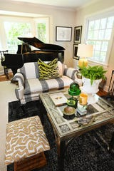 An antique piano adds a focal point to the inviting living room, which is situated at the front of the house and looks out over the street.