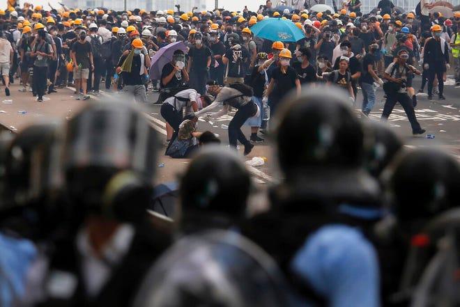 Protesters help a fallen person after clashing with riot police during a massive demonstration outside the Legislative Council in Hong Kong, Wednesday, June 12, 2019. Hong Kong police fired tear gas and rubber bullets at protesters who had massed outside government headquarters Wednesday in opposition to a proposed extradition bill that has become a lightning rod for concerns over greater Chinese control and erosion of civil liberties in the territory.