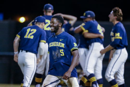Christan Bullock (5) celebrates after Michigan defeated UCLA to advance to the College World Series.
