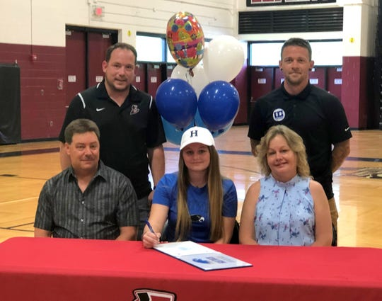 Elmira senior Loni Harris signs to play women's soccer at Hartwick College on June 12, 2019 at Elmira High School's gym. Next to her are her parents, Lon Harris and Kim Harris. In the back, from left, Elmira girls soccer coach Zach Sarno  and Hartwick head coach Brian Knapp.