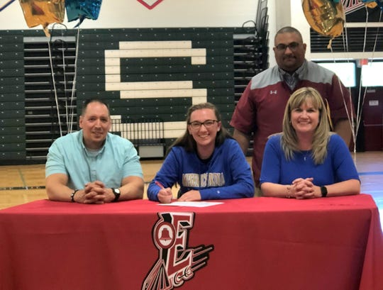 Elmira senior Alexa Wagner signs to compete in track and field at Misericordia University on June 12, 2019 at the Elmira High School gym. Next to her are her parents, Jim Wagner and Christa Wagner. In the back is Elmira track coach David Perkins.