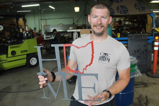 Christy Machine owner Alex Robinson shows off one of the company's custom-designed pieces of metal art at the company's Fremont location.